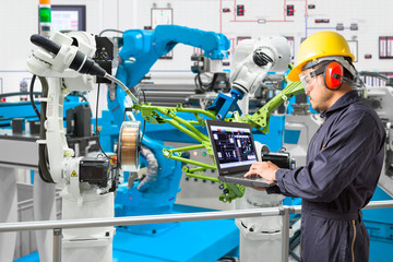 Engineer using laptop computer maintenance automatic robotic welding with robot workpiece in automotive industry, Smart factory concept
