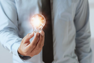 hand businessman holding light bulb, innovation and inspiration idea concept