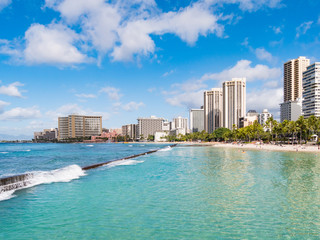 Blue Waters of Queens Beach and pier in Waikiki with Hotels in the distance, Honolulu, Oahu Island, Hawaii, USA. Waikiki Beach in the center of Honolulu has the largest number of visitors in Hawaii.