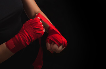 Female boxer is wrapping hands with red wrap, black background with copy space. Strong, ready for fighting or sparring. Women self defense.