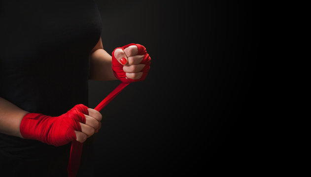 Woman is wrapping hands with red boxing wraps on black background with copy space. Strong hand and ready for fight, active exercise and sparring.  Women self defense.