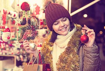 girl choosing Christmas decoration at market