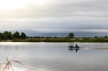 Fisherman on motor boat on lake.