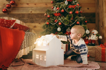 Happy cute little baby boy dressed in sweater sitting at the Christmas tree with a toy magic white house in wooden room at home. Child good mood. New Year. Lifestyle, family and holiday 2018 concept