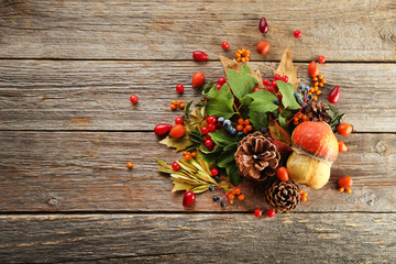 Autumn leafs with berries on grey wooden table