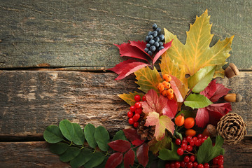 Autumn leafs with berries and nuts on wooden table