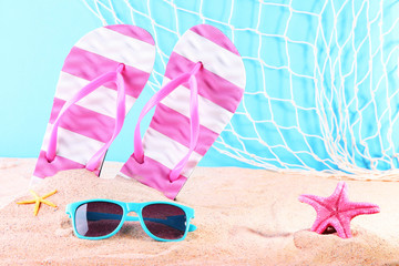 Flip flops with sunglasses and starfish on the beach sand