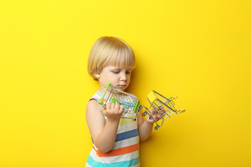 Portrait of little boy with small shopping carts on yellow background