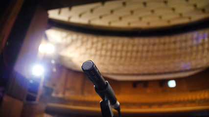 Microphone on the stage and empty hall during the rehearsal. Microphone on stage with stage-lights in the background. Microphone on the stage in the empty hall