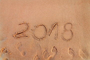 New Year written on sandy beach 2018 is coming  like date holiday concept