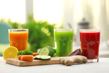Glasses with various fresh vegetable juices on table