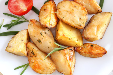 Delicious baked potatoes with rosemary on plate, closeup
