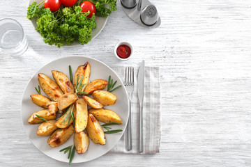 Composition with plate of delicious rosemary potatoes on table