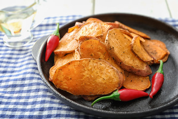 Frying pan with yummy sweet potato chips on table