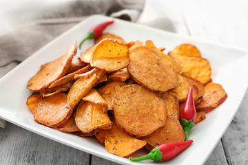 Plate with yummy sweet potato chips on table