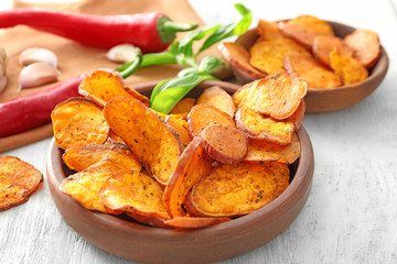 Bowl with yummy sweet potato chips on table