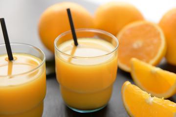 Glasses of fresh orange juice on slate plate