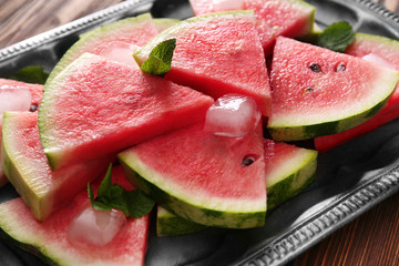 Tray with tasty sliced watermelon on table