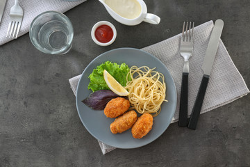 Plate with tasty salmon croquettes and spaghetti on table
