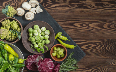 Variety of organic fresh vegetables on wooden background