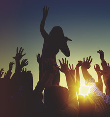 Silhouettes of a music concert at sunset