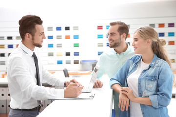 Car salesman and young couple in dealership