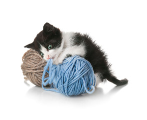 Cute funny baby kitten playing with ball of thread on white background