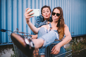 Young adult hipster girlfriends taking selfie and pulling funny faces