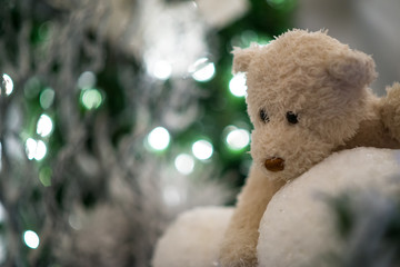 teddy bear hugs snowballs with blue christmas tree and lights blurred in the background.