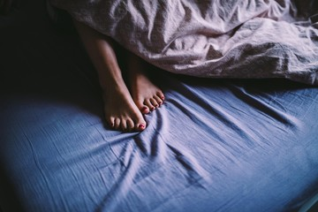 Close-up of feet sticking out of blanket in bed