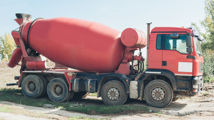 Red concrete mixer vehicle on the construction site
