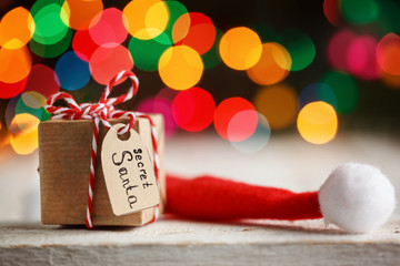 Christmas present or box for secret santa with Santa hat. Greeting card.