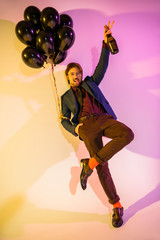 excited man with champagne and balloons
