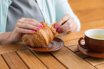 Woman with pink manicure is tearing a small piece from large croissant , aliened