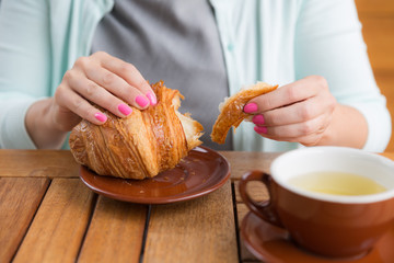 Woman with pink manicure is tearing a small piece from large croissant, looking straight