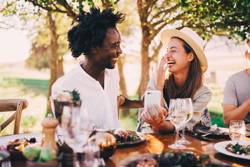 Mixed race couple having fun with phone at dinner party