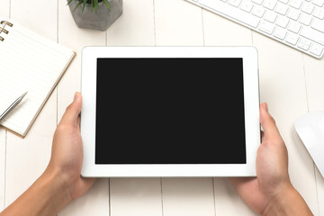 Man holding digital tablet with copy space while sitting at wooden desk, top view