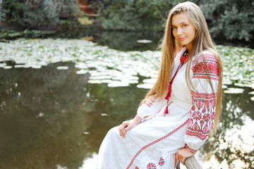 Beautiful slavonic girl with long blond hair and blue eyes sitting near river