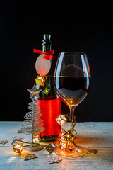 New Year's image of bottle with red ribbon, Christmas tree toys, wine glass