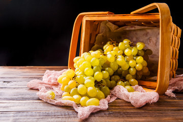 Image of wooden basket with green grapes on table