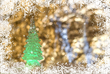 A glass Christmas toy, a green Christmas tree on a snow golden  blurred  background