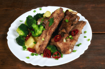 roasted pork ribs with potatoes and broccoli on an old wooden table