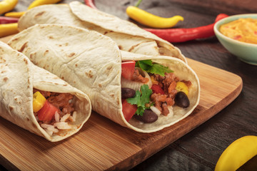 Closeup of Mexican burritos with beef, rice, and chili peppers