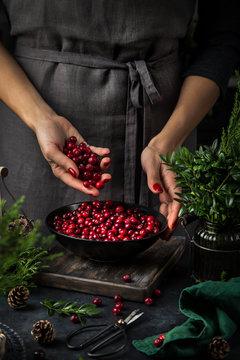 fresh cranberry in woman hands. Dark kitchen table