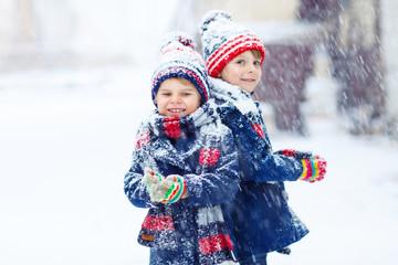 Happy children having fun with snow in winter