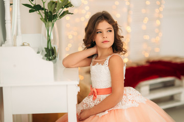 Little beautiful girl with brown hair in a Peach-colored dress. Poses for a photographer