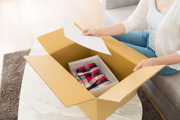 woman opening personal online shopping parcel