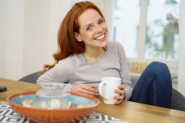 frau sitzt zuhause am tisch mit einer tasse tee