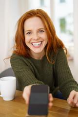 lachende frau zeigt ihr mobiltelefon