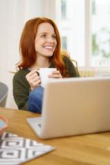 frau sitzt entspannt mit laptop und einer tasse tee zuhause am tisch
